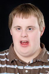 Teenage boy with Downs Syndrome smiling,