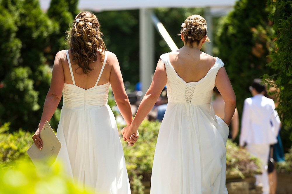 Toronto, Ontario ---2014-06-26--- Cheryl Taylor and Jennifer Smith hold hands as they arrive for the Grand Pride Wedding, a mass gay wedding at Casa Loma in Toronto, Canada June 26, 2014. The celebration which saw over 100 couples tie the knot was part of the World Pride festival running in the city this week.<br /> GEOFF ROBINS AFP