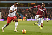Aston Villa striker Jonathan Kodjia (26) flys in to tackle Nottingham Forest midfielder Tendayi Darikwa (27) during the EFL Sky Bet Championship match between Aston Villa and Nottingham Forest at Villa Park, Birmingham, England on 28 November 2018.
