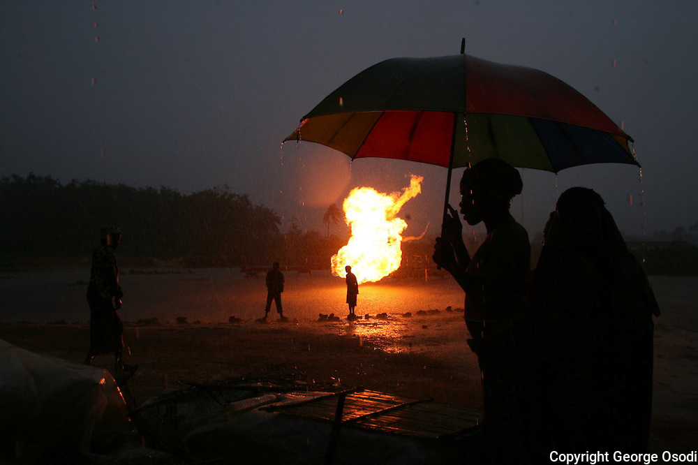 .Ethnic Urhobo Women take shelter while it rains as the dry tapioca alongside a Shell Oil gas flare in Utorogu, near Warri in Nigeria's oil-rich delta region, Wednesday, Nov. 8, 2006. Despite it's oil and natural gas riches, the delta region remains one of the most impoverished regions of Nigeria. Delta residents accuse successive Nigerian governments and international oil companies of depriving them of the wealth pumped from their backyards. Attacks this year by militant groups fighting for greater local control of the country's oil wealth, as well as criminal gangs in the delta, have reduced Nigeria's exports by roughly 500,000 barrels a day. Nigeria in Africa's biggest oil exporter and supplies about 10 % of US oil and has been growing in importance as a supplier. Oil accounts for about 95 % of the country's exports. But the delta is a volatile cocktail of warlords, oil thieves, corrupt government officials and unemployed youths.(/George Osodi)  ..