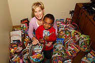 Janet Fernandes of Dayton with Jeff, 2, a little brother at the Big Brothers Big Sisters of the Greater Miami Valley office in Moraine, Saturday, March 23, 2013.  Jeff is here to pick up one of the 200 Easter baskets Fernandes prepared this year.  Some are picked up and some are distributed in schools before the Spring  break.  She says she started making baskets for others a few years ago with 'leftovers,' but now she and friends start shopping for baskets and other supplies the day after Easter each year, and prepare between two and three hundred each year.