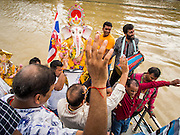 """15 SEPTEMBER 2013 - BANGKOK, THAILAND: Hindus in Bangkok sing and praise Ganesha before pushing the statues of Ganesha into the Chao Phraya River on the last day of Ganesha Chaturthi celebrations at Shiva Temple in Bangkok. Ganesha Chaturthi is the Hindu festival celebrated on the day of the re-birth of Lord Ganesha, the son of Shiva and Parvati. The festival, also known as Ganeshotsav (""""Festival of Ganesha"""") is observed in the Hindu calendar month of Bhaadrapada. The festival lasts for 10 days, ending on Anant Chaturdashi. Ganesha is a widely worshipped Hindu deity and is revered by many Thai Buddhists. Ganesha is widely revered as the remover of obstacles, the patron of arts and sciences and the deva of intellect and wisdom. The last day of the festival is marked by the immersion of the deity, which symbolizes the cycle of creation and dissolution in nature.  In Bangkok, the deity (statue) was submerged in the Chao Phraya River.         PHOTO BY JACK KURTZ"""