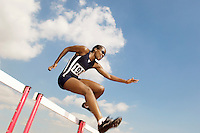 Female athlete jumping hurdle