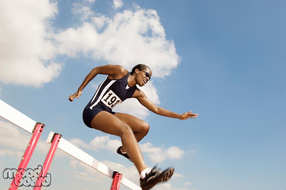 Female athlete jumping hurdle