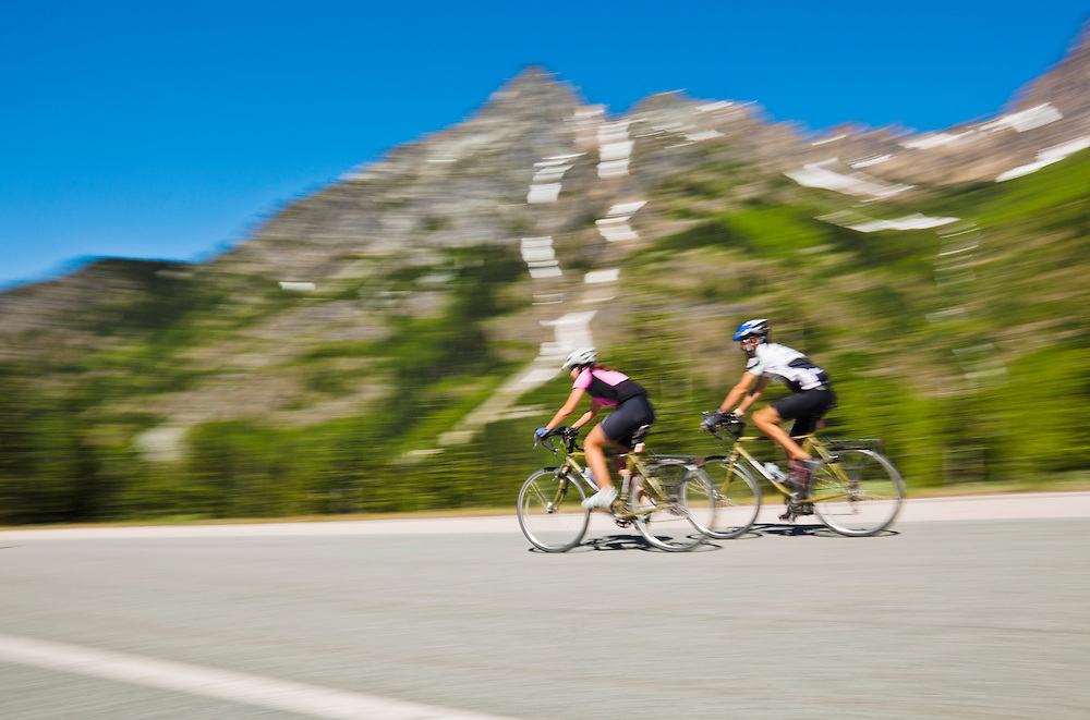 A young man and woman riding their bicycles on Highway 20 in the North Cascades of Washington State.