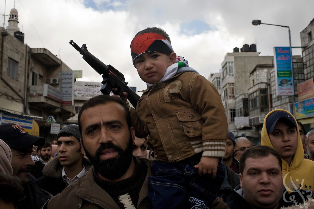 A Palestinian boy with a toy rifle rides on the shoulder of his father during a protest against the ongoing Israeli incursion into Gaza January 09, 2009 in the West Bank City of Ramallah. Scuffles broke out during the protest of more than 10,000 marchers between supporters of Fatah, and Hamas.