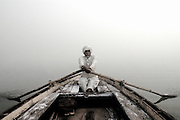 Ram Ji, a boatman who works on the Ganges River in Varanasi, India rows tourists in his boat to earn his living.