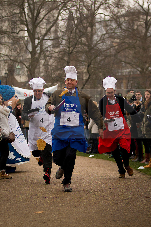 © Licensed to London News Pictures. 12/02/2013. London, UK. Lord Redesdale (C), Liberal Democrat MP Martin Horwood (L) and Patrick Wintour of the Guardian (R) toss pancakes as they take part in the annual Rehab Parliamentary Pancake Race in Westminster, London today (12/02/2013).The race involving MPs from the House of Commons, Lords from the House of Lords and members of the Parliamentary Press Gallery, is aimed at raising awareness for the Rehab; a charity that works to support people with disabilities, takes place every year in Victoria Tower Gardens next to Parliament and was won this year by the House of Commons team. Photo credit: Matt Cetti-Roberts/LNP