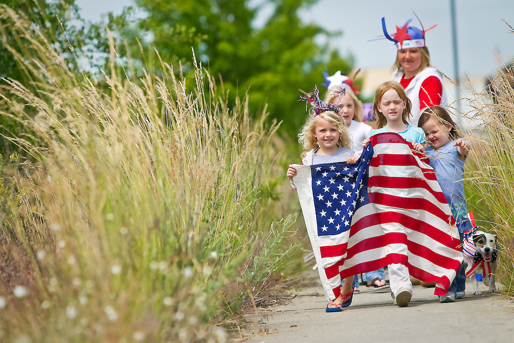 Joely Gardiner, left, Emma Marks and Ellie Deaton lead a patriotic parade as they march along a overgrown section of sidewalk near Cottage Childcare and Learning.