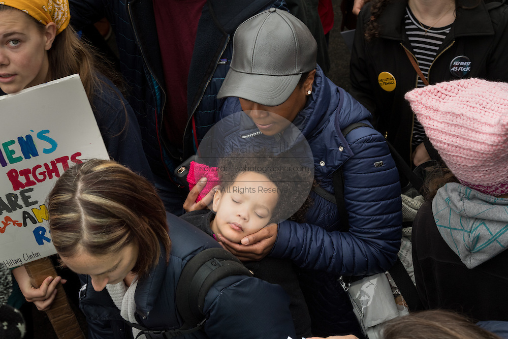 A young child is carried sleeping through crowds of demonstrators during the Women's March on Washington in protest to President Donald Trump January 21, 2017 in Washington, DC. More than 500,000 people crammed the National Mall in a peaceful and festival rally in a rebuke of the new president.