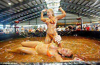 Women wrestle in chocolate sauce at a Harley-Davison anniversary party in Milwaukee August 29, 2003. The legendary American motorcycle company is celebrating its 100th anniversary and is expected to draw 200,000 to 300,000 people to the companies home base over four days.    REUTERS/Rick Wilking