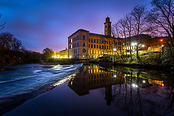 © Licensed to London News Pictures. 30/03/2020. Saltaire UK. The Bradford District NHS Trust housed at Salts mill in the Victorian model village of Saltaire reflects into the River Aire at dawn this morning in Yorkshire as the UK continues the Coronavirus Lockdown. Photo credit: Andrew McCaren/LNP