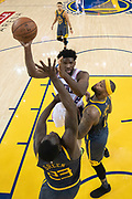 January 31, 2019; Oakland, CA, USA; Philadelphia 76ers center Joel Embiid (21) shoots the basketball against Golden State Warriors forward Draymond Green (23) and center DeMarcus Cousins (0) during the second half at Oracle Arena.