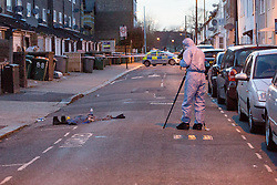 © Licensed to London News Pictures. 25/03/2016. London, UK. A forensic officer photographs personal effects in the road within the police cordon in Tower Hamlets Road, behind Magpie Close in Forest Gate, east London. Five people have been taken to hospital, with one man in a critical condition. Photo credit : Vickie Flores/LNP