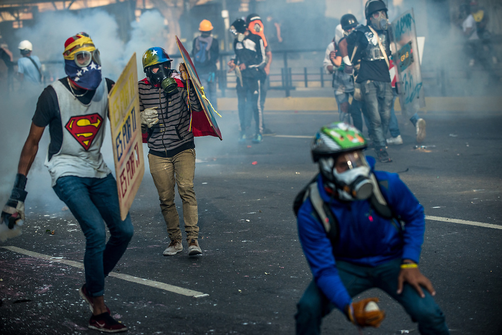CARACAS, VENEZUELA - MAY 20, 2017:  Anti-government protesters take cover behind homemade shields during clashes with the National Police.  The streets of Caracas and other cities across Venezuela have been filled with tens of thousands of demonstrators for nearly 100 days of massive protests, held since April 1st. Protesters are enraged at the government for becoming an increasingly repressive, authoritarian regime that has delayed elections, used armed government loyalist to threaten dissidents, called for the Constitution to be re-written to favor them, jailed and tortured protesters and members of the political opposition, and whose corruption and failed economic policy has caused the current economic crisis that has led to widespread food and medicine shortages across the country.  Independent local media report nearly 100 people have been killed during protests and protest-related riots and looting.  The government currently only officially reports 75 deaths.  Over 2,000 people have been injured, and over 3,000 protesters have been detained by authorities.  PHOTO: Meridith Kohut