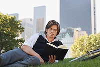 Man lying on lawn holding book portrait