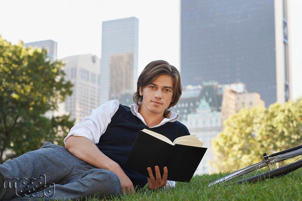 Man lying on lawn holding book portrait