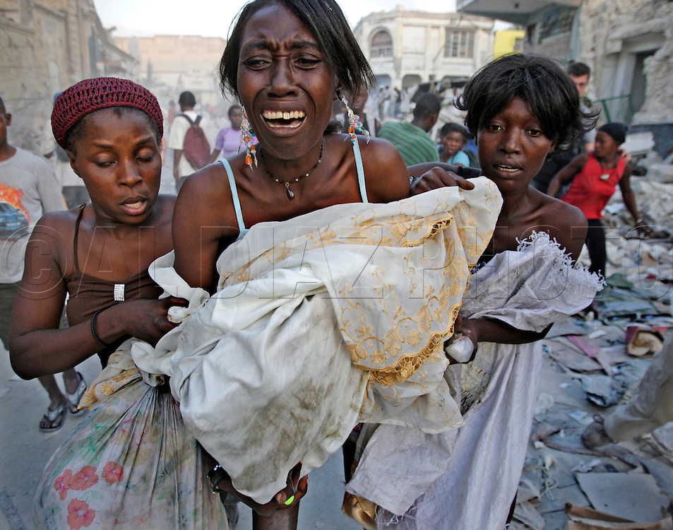 Haitian women attempt to salvage their belongings but are assaulted by looters as Haitians fight each other in the warehouse district of Port au Prince, Haiti. The 2010 earthquake ravaged the capital city causing a desperate search for supplies.