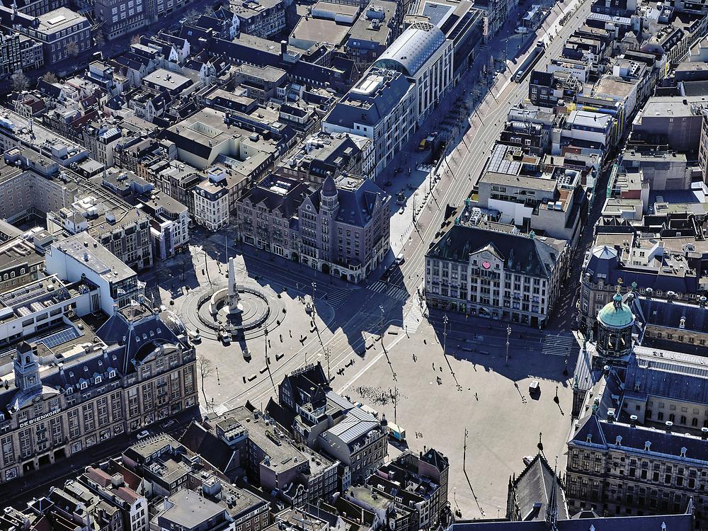 Nederland, Noord-Holland, Amsterdam; 23-03-2020; Dam en Damplein, ongehoord stil op vrachtauto's en een politieauto na. Geen drommen toeristen of dagjesmensen. De Bijenkorf aan het Damrak is gesloten, nauwelijks autoverkeer op het Damrak en Rokin. Het publieke leven in het centrum van de hoofdstad is bijna geheel stil komen te liggen als gevolg van het Corona virus. Niet alleen is alle horeca dicht, ook veel winkels en andere bedrijven zijn gesloten. Het publiek blijft over het algemeen binnen, de straten en pleinen zijn stil.<br /> Dam square is incredibly quiet, no crowds of tourists or day trippers.<br /> Public life in the center of the capital has come to a complete standstill as a result of the Corona virus. Not only are all pubs, coffee shops and restaurants,  closed, many shops and other companies are also closed. The public generally stays inside, the streets and squares are very quiet.<br /> <br /> luchtfoto (toeslag op standaard tarieven);<br /> aerial photo (additional fee required)<br /> copyright © 2020 foto/photo Siebe Swart