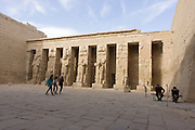 Women tourists walk past tall Ramessid columns in the peristyle court at the ancient Egyptian site of Medinet Habu (1194-1163BC), the Mortuary Temple of Ramesses III in Luxor, Nile Valley, Egypt. Medinet Habu is an important New Kingdom period structure in the West Bank of Luxor in Egypt. Aside from its size and architectural and artistic importance, the temple is probably best known as the source of inscribed reliefs depicting the advent and defeat of the Sea Peoples during the reign of Ramesses III.