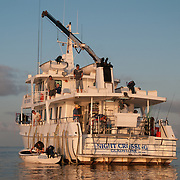The Night Crossing, a fishing charter ship based in Gladstone, is bathed in golden late afternoon sunlight as the crew prepares the boat for the night on the Great Barrier Reef, Australia. The crane is extended to lift the small dinghies on top of the boat.