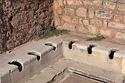 The latrine or public toilets, 1st century AD, Ephesus, Izmir, Turkey. The toilets were part of the Scholastica Baths but were also open to the paying public. <br /> They are off the covered Academy Street and are arranged around 3 sides of an open colonnaded courtyard. Fresh water was available for washing in the channel and a pool, while a drainage system underneath dealt with sewage. Ephesus was an ancient Greek city founded in the 10th century BC, and later a major Roman city, on the Ionian coast near present day Selcuk. Picture by Manuel Cohen