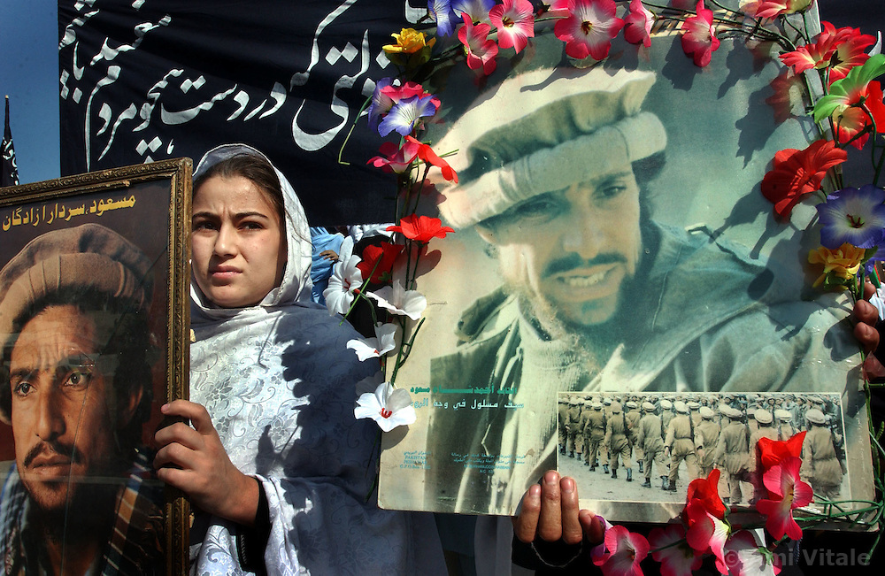 KABUL,AFGHANISTAN - SEPT. 9: An Afghan girl holds a portrait of Ahmad Shah Massoud during a ceremony in Kabul Sports Stadium, September 9, 2002  to comemerate the anniversary of his death. (Photo by Ami Vitale/Getty Images)