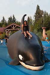 United States, Washington, Bellevue, children playing at whale fountain at playground in Crossroads Park