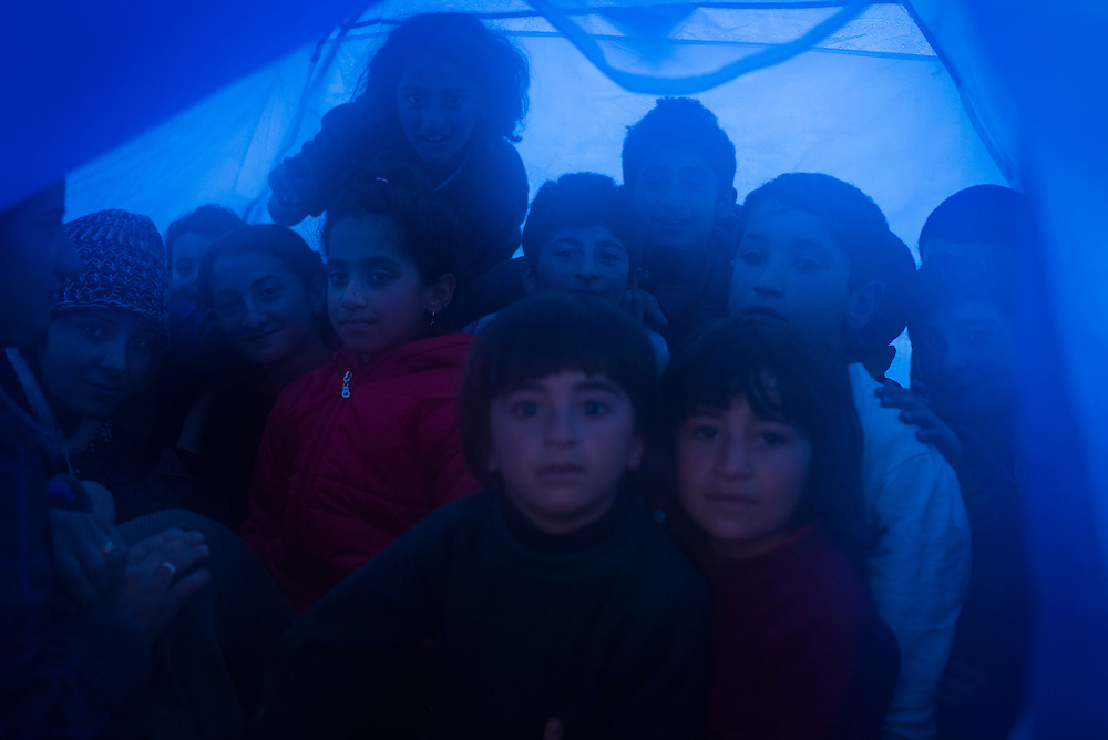 Fourteen refugees, the majority of them children, pose for a portrait in a tent originally meant for two people at a camp on the Macedonian (FYROM) border on March 9, 2016 in Idomeni, Greece. With rain pounding the camp, refugees huddled together in progressively smaller spaces in an effort to stay dry and warm.