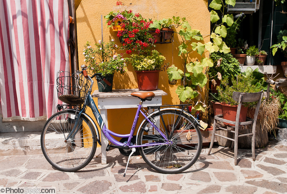 "Woman's bicycle, potted plants, chair. Burano, known for knitted lacework, fishing, and colorfully painted houses, is a small archipelago of four islands linked by bridges in the Venetian Lagoon, northern Italy, Europe. Burano's traditional house colors are strictly regulated by government. The Romans may have been first to settle Burano. Romantic Venice (Venezia), ""City of Canals,"" stretches across 117 small islands in the marshy Venetian Lagoon along the Adriatic Sea in northeast Italy, between the mouths of the Po (south) and Piave (north) Rivers. Venice and the Venetian Lagoon are honored on UNESCO's World Heritage List."