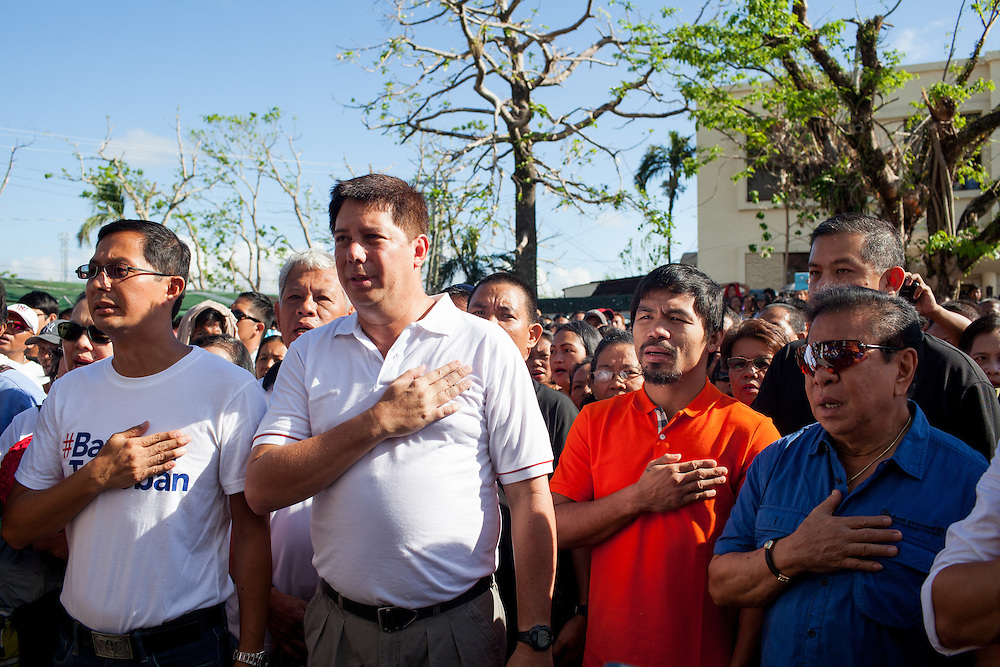 L-R Jimmy Sambo Yaokasin, Vice Mayor of Tacloban City; Mayor Alfred Romualdez; and Manny Pacquaio salute during the Philippines national anthem.<br /> <br /> Manny Pacquiao visits victims of Typhoon Yolanda in Tacloban City.  Leyte, Philippines  December 2, 2013