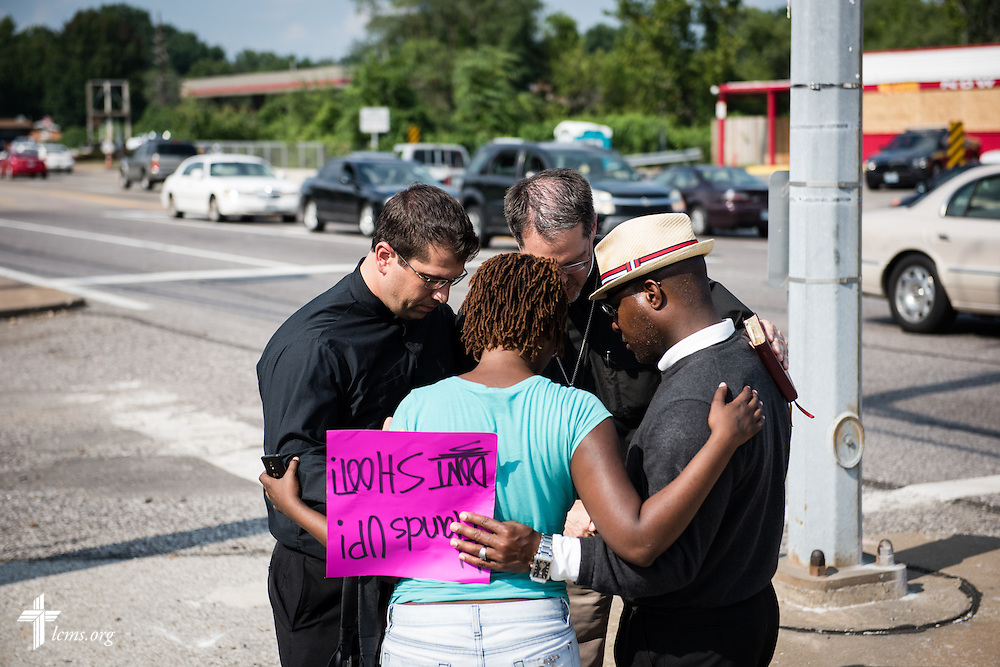 The Rev. Ross Johnson, director of LCMS Disaster Response, and the Rev. Steve Schave, director of LCMS Urban and Inner City Mission, pray with others on Monday, August 18, 2014, along West Florissant Avenue in Ferguson, Mo. LCMS Communications/Erik M. Lunsford