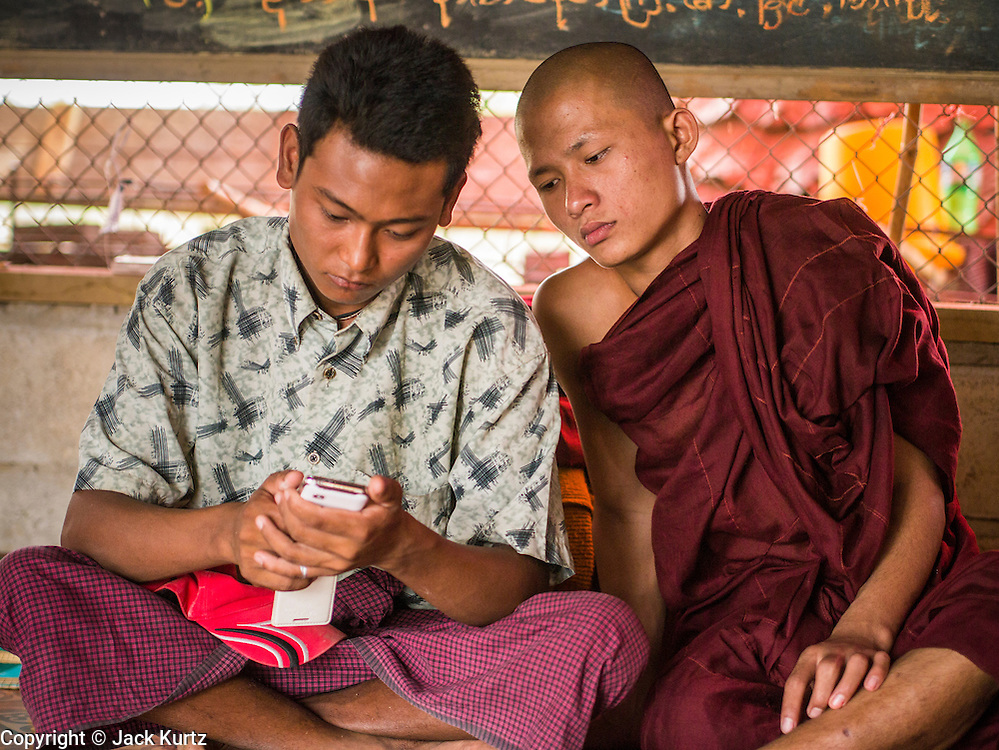 25 MAY 2013 - MAE SOT, TAK, THAILAND: A Burmese man and a novice watch videos on a smart phone in their temple in an unofficial village of Burmese refugees north of Mae Sot, Thailand. They live on a narrow strip of land about 200 meters deep and 400 meters long that juts into Thailand. The land is technically Burma but it is on the Thai side of the Moei River, which marks most of the border in this part of Thailand. The refugees, a mix of Buddhists and Christians, settled on the land years ago to avoid strife in Myanmar (Burma). For all practical purposes they live in Thailand. They shop in Thai markets and see their produce to Thai buyers. About 200 people live in thatched huts spread throughout the community. They're close enough to Mae Sot that some can work in town and Burmese merchants from Mae Sot come out to their village to do business with them.   PHOTO BY JACK KURTZ
