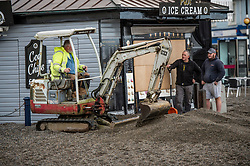 © London News Pictures. 22/10/2017. Aberystwyth,UK. Work begins on clearing tons of sand and shale from in front of his  cabin on the promenade. After two days of winds, the tail end of storm Brian is still battering the seafront and promenade in Aberystwyth on the Cardigan Bay coast of west wales. Photo credit: Keith Morris/LNP