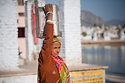 Indian woman carry a box on her head by Pushkar lake (India)