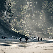 Two male surfers walking with their surfboards on the beach in Oswald West State Park, Oregon Coast.