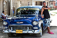 Man with his 1950's Chevrolet posing in pink crocs showing his Che tattoo in Holguin, Cuba.