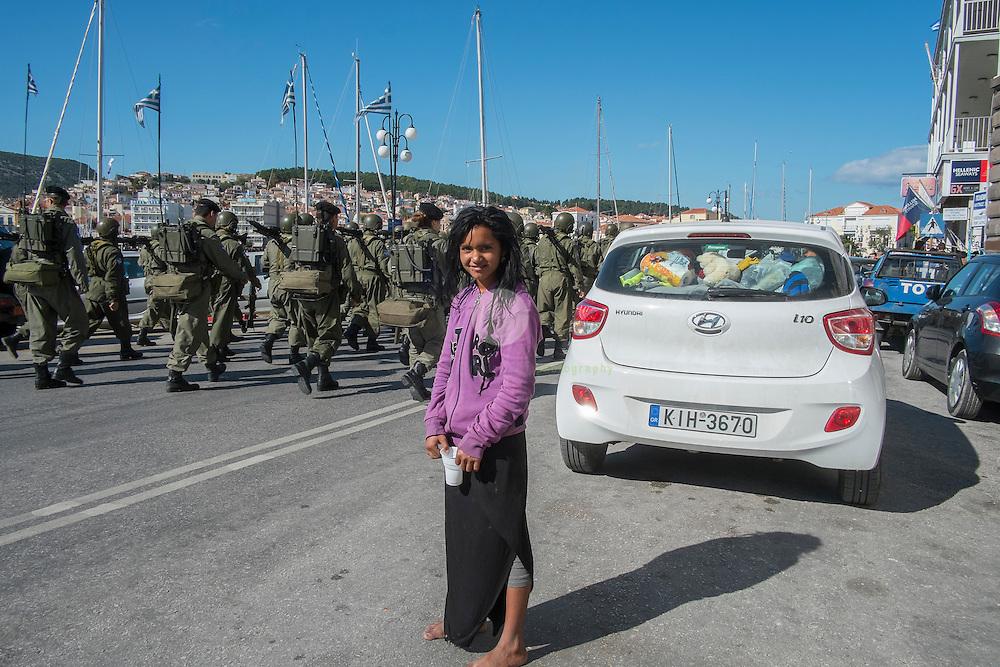 GRIECHENLAND, Lesbos, Hauptstadt Mytilini. 27.10.2015 / Griechischer Nationalfeiertag: ein kleines Maedchen steht ohne Schuhe - und mit einen Becher für Spenden - am Strassenrand, waehrend Soldaten anlaesslich des Nationalfeiertags marschieren.