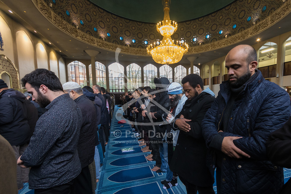 Regents Park Mosque, London, February 5th 2017. Dozens of curious non-Muslims are welcomed at Regent's Park Mosque in London as part of the Muslim Council of Britain's annual 'Visit My Mosque Day'. Visitors were able to observe prayers and we shown around the mosque by members, where there was a exhibition of the history and teachings of Islam. PICTURED: Men line up to pray as visitors observe from the back of the Men's Prayer Hall.