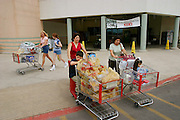 Diana Fernandez and her mother, Alejandrina Cepeda, depart from the local H-E-B supermarket in San Antonio, Texas after shopping for a weeks' worth of food. Helping to push Diana's shopping cart is her son Brian while her daughter, Brianna, is happily getting a ride from her grandmother. (Supporting image from the project Hungry Planet: What the World Eats.)