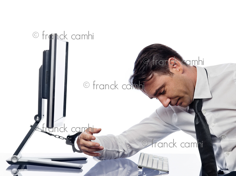 one caucasian man chained to computer with handcuffs expressing addiction concept isolated studio on white background