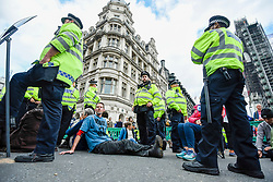 © Licensed to London News Pictures. 08/10/2019. LONDON, UK.  Members of the police force decide how to deal with climate activists staging a sit-in in Parliament Square, on day two of Extinction Rebellion's protest which is planned to close-down Westminster and other areas in the capital for two weeks.  Demonstrators are calling on the Government's immediate action to tackle the negative effects of climate change.  Photo credit: Stephen Chung/LNP