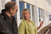 ICE.MWdrv05.18.xrw..Margret (Linda) Gunnlaugsdottir, 52, who works part time at the Maritime Museum in Reykjavik, Iceland takes a smoking break when her husband Bennie, a retired airline pilot stops by for a visit. Ten years ago they and their family were the Icelandic participants in Material World: A Global Family Portrait, 1994 for which they took all of their possessions out of their house for a family and possessions portrait in the snow. Pages 162-163. Cigarette. {{Central image from original book project is: ICE.mw.01.xxs.}}.