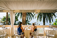 GARDONE RIVIERA, ITALY - 20 APRIL 2018: Clients of The Grand Hotel Fasano have breakfast, here in Gardone Riviera, Italy, on April 20th 2018.<br /> <br /> Lake Garda is the largest lake in Italy. It is a popular holiday location located in northern Italy, about halfway between Brescia and Verona, and between Venice and Milan on the edge of the Dolomites. The lake and its shoreline are divided between the provinces of Verona (to the south-east), Brescia (south-west), and Trentino (north).