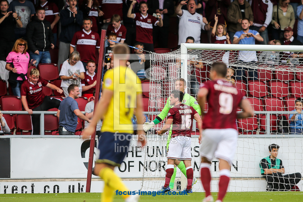 Adam Smith of Northampton Town (centre) is congratulated after saving a penalty during the Sky Bet League 2 match at Sixfields Stadium, Northampton<br /> Picture by Andy Kearns/Focus Images Ltd 0781 864 4264<br /> 12/09/2015