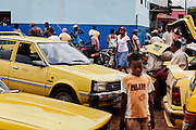 Next to yellow taxis, people are busy walking around a market on the island of Sao Tome, Sao Tome and Principe, (STP) a former Portuguese colony in the Gulf of Guinea, West Africa.