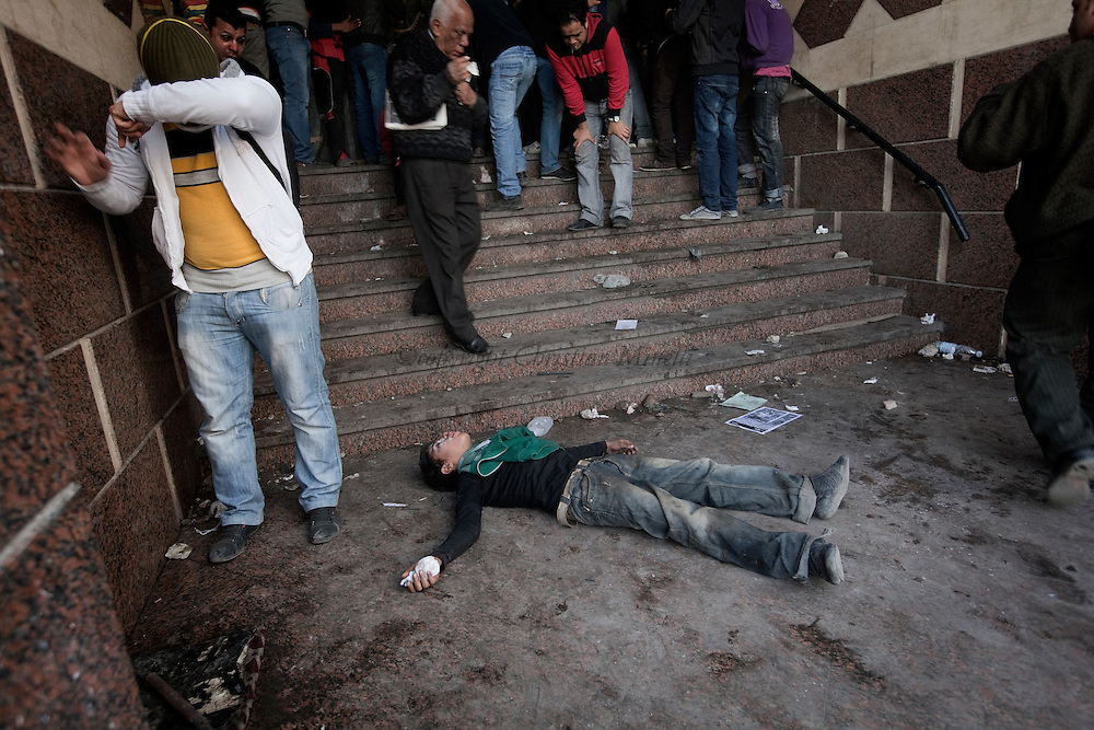 EGYPT, Cairo :  An Egyptian child lies on the ground after breathing a tear gas during clashes with police near the interior ministry in Cairo on February 3, 2012. Egyptian protesters clashed with police for a second straight day as anger against the ruling military mounted..