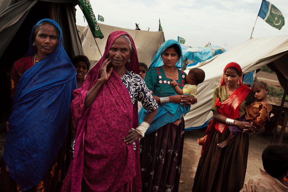 Women (from left; Shanti, 40 years old, has seven children, Lachmi, 65 years old, Heeri, 20 years old,  has three children, Jianni, 22 years old, has two children)  relate their experience of escaping floods to a temporary camp at Digri Bypass in Mirpur Khas district, Sindh, Pakistan on November,  2011. They have been there six weeks and are waiting for housing aid to rebuilt their homes. In August 2011, Heavy monsoon rains triggered flooding in lower parts of Sindh and northern parts of Punjab