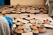 Women cover pots of stew with cardboard and with baskets for the wedding feast.