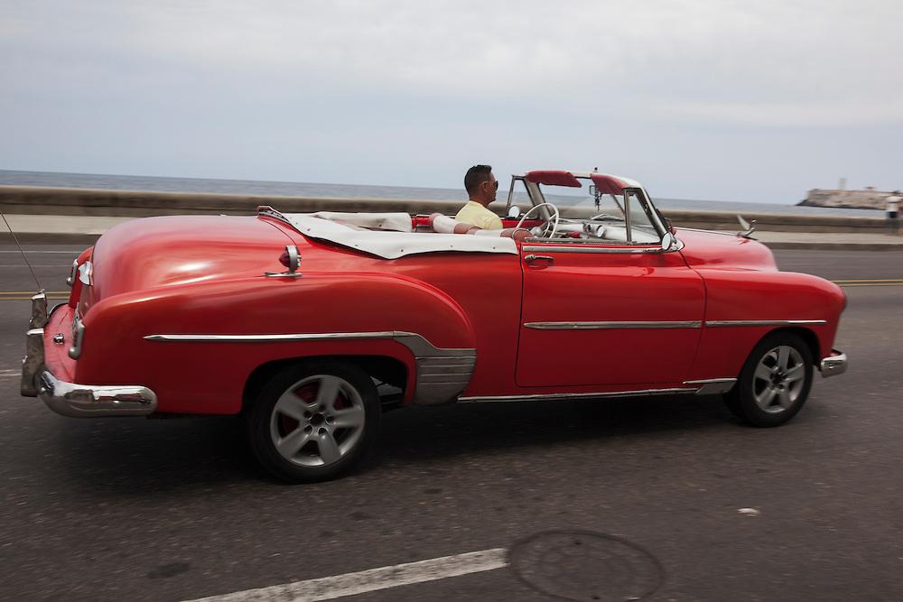 Old American convertible cruising down Malecon Avenue in Havana, Cuba.